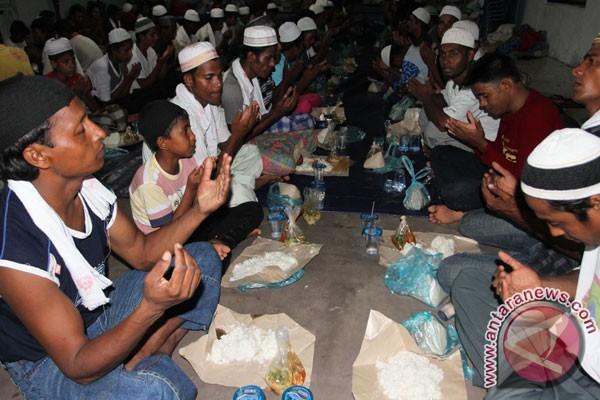 Puluhan imigran etnis Rohingya, Myanmar dan Bangladesh berdoa sebelum menyantap makanan di lokasi penampungan sementara, Pangkalan Susu, Langkat, Sumatera Utara, Ahad (17/5) malam.