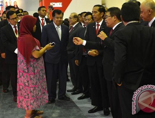 Sumber: www.antaranews.com Presiden Joko Widodo (keempat kanan) didampingi Wapres Jusuf Kalla mendapat penjelasan tentang produk dan layanan dari Dirut Telkom Alex Sinaga (ketiga kanan) saat meninjau stan Telkomsel di World Islamic Economic Forum (WIEF) Ke-12 di Jakarta Convention Center, Jakarta, Selasa (2/8).